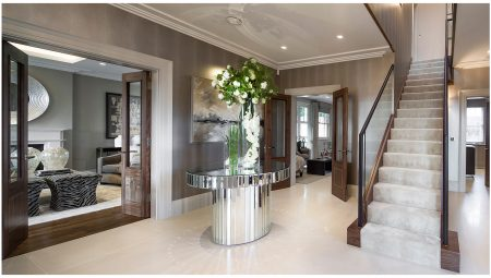 Decorative features in neutral toned entrance hall comprise, simple stepped cornice, glass balustrades, leather handrails, stair carpet runner, mirrored table, and part glazed double doorsets