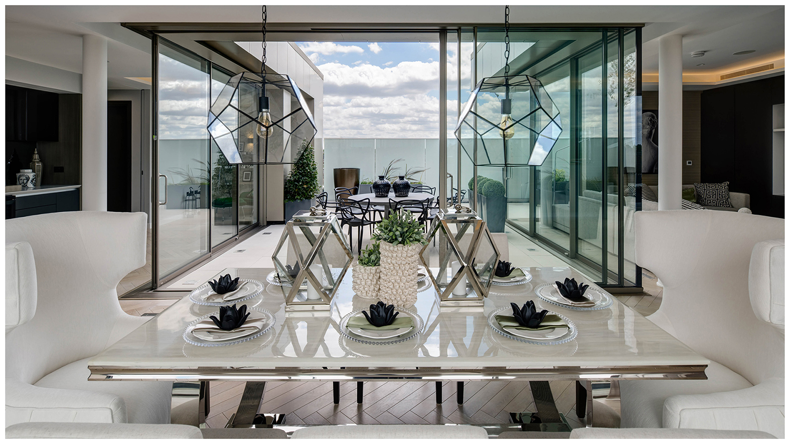 Open plan indoor and outdoor dining areas with unobstructed access through flexible sliding floor to ceiling glass walls and plush statement seating