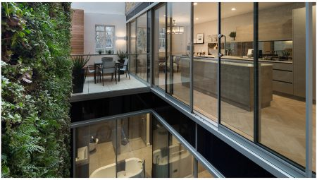 Visual connectivity between floors and living spaces, through glass façade, showcasing the open-plan kitchen and living spaces and view into master bathroom