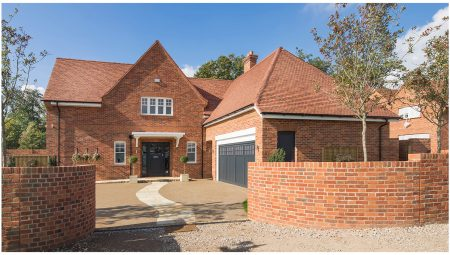View from pavement up onto a large red brick detached house with front double garage. A curved brick boundary wall encases the property.